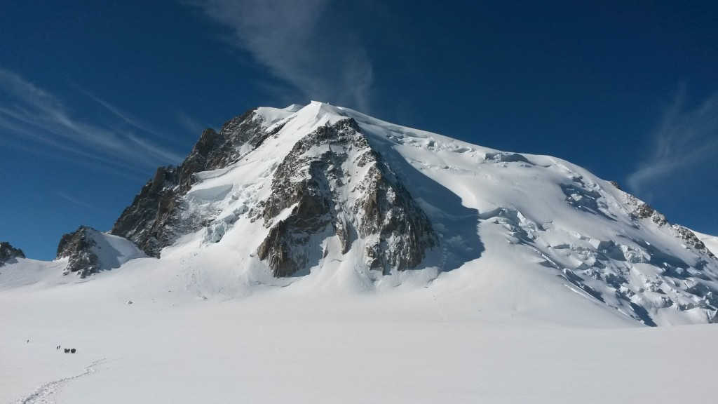 "The Mont Blanc du Tacul. The Tacul Triangle is in the center and Pointe Lachenal is the small bump on the left side. The normal route up Tacul goes up the righthand snow slop, following closely the edge of the shadow. Our route - Contamine-Grisolle - starts left of the triangle, then goes up the snow ""spike"" pointin to the center and then pretty much straight up the rock and snow bands."